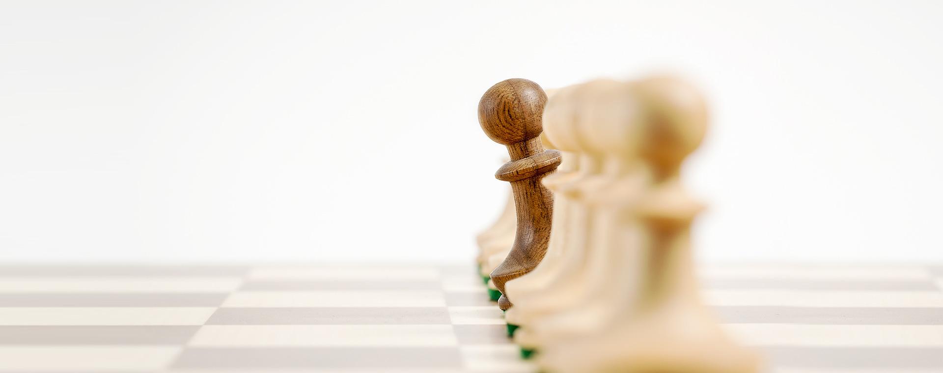 Schachbrett mit weißen Schachfiguren und einer hervorschauenden braunen Figur