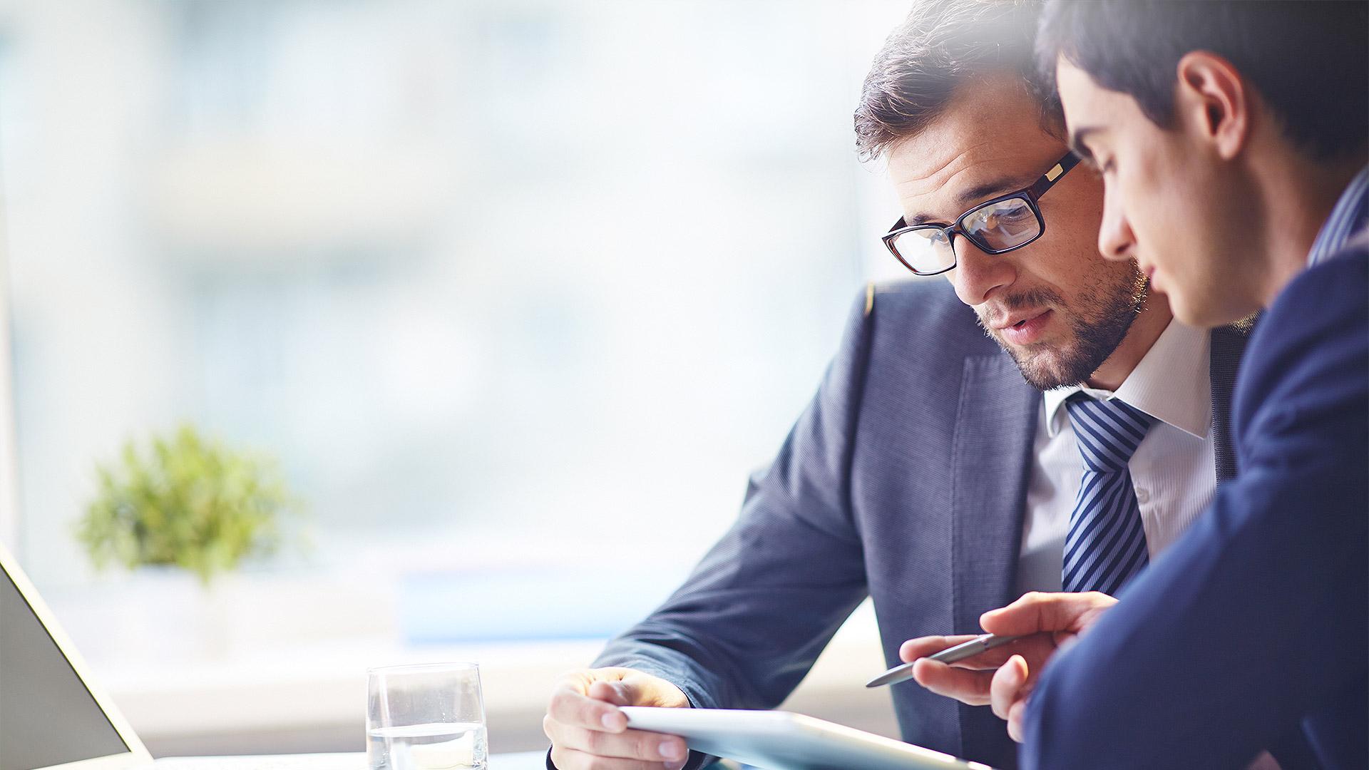 Zwei Männer im Anzug sitzen nebeneinander und schauen sich Ergebnisse an